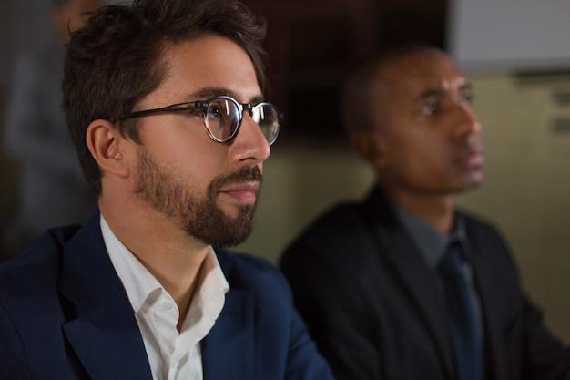 Biznesmen w eyeglasses pracuje w ciemnym biurze