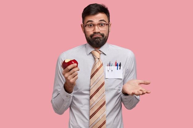Biznesmen w formalne ubrania trzyma jabłko