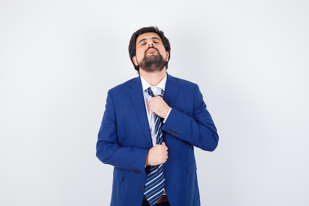 Biznesmen w formalnym garniturze próbuje zdjąć krawat i wygląda na zmęczonego, widok z przodu.