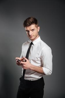 Biznesmen w formalwear mienia telefonie komórkowym