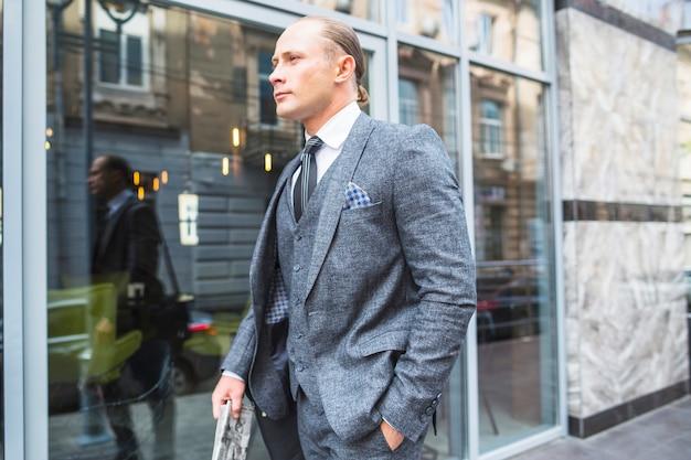 Biznesmen w garnitur stojący przed szklanym oknem