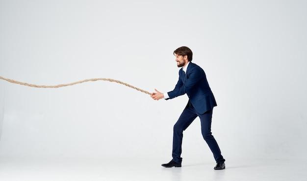 Biznesmen w garniturze ciągnie za światło w studio liny