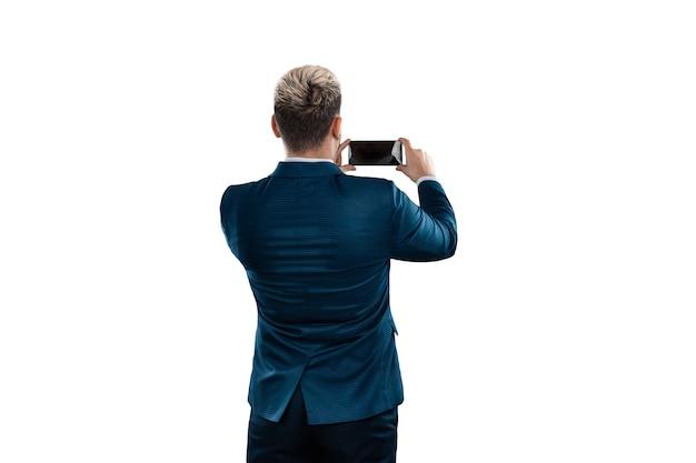 Biznesmen w garniturze coś fotografuje