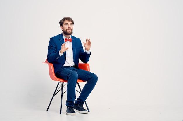 Biznesmen w garniturze czerwonym krześle profesjonalna pewność siebie