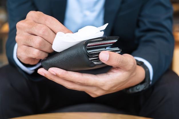 Biznesmen w garniturze czyści portfel pieniędzy wilgotnymi chusteczkami i środkiem dezynfekującym alkoholem w biurze lub kawiarni, ochrona przed zakażeniem koronawirusem (covid-19). nowa koncepcja normalnej i czystej powierzchni