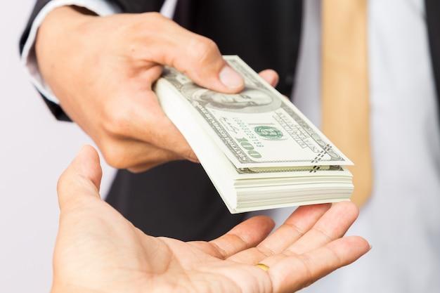 Biznesmen w garniturze daje mężczyznom dolary amerykańskie