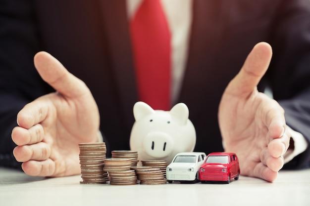 Biznesmen w garniturze dłoń trzymająca model autka na białym tle ponad dużo pieniędzy ułożonych w stos monet koncepcja ubezpieczenia, kredytu i zakupu samochodu oszczędność skarbonki