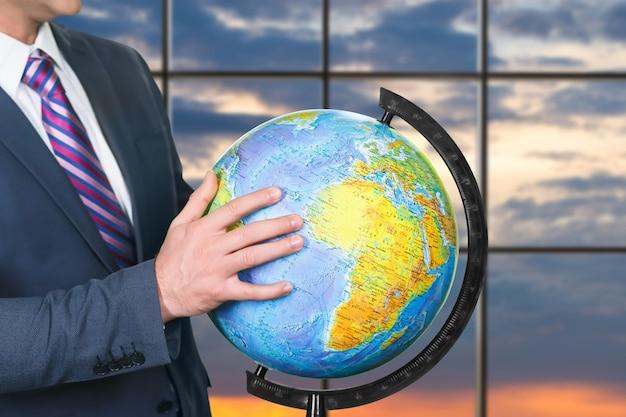Biznesmen w garniturze dotyka kuli ziemskiej. globus na tle nieba wschód słońca. ręka postępu. zakręć tym światem.