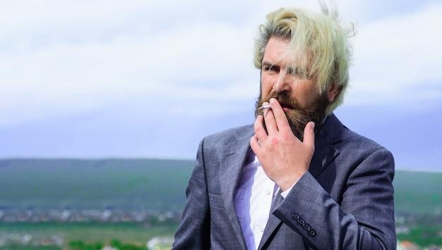 Biznesmen w garniturze dym papierosowy. człowiek palenia. stylowy brodaty mężczyzna z papierosem.