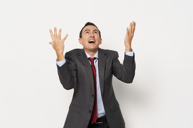 Biznesmen w garniturze emocje gestykuluje ręce studio na białym tle