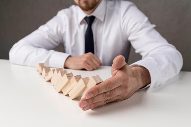 Biznesmen w garniturze i krawacie, trzymając kawałki domina