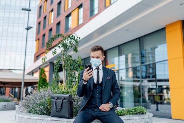 Biznesmen w garniturze i masce medycznej wiadomości na smartfonie, stojąc na ulicy miasta w pobliżu współczesnych budynków