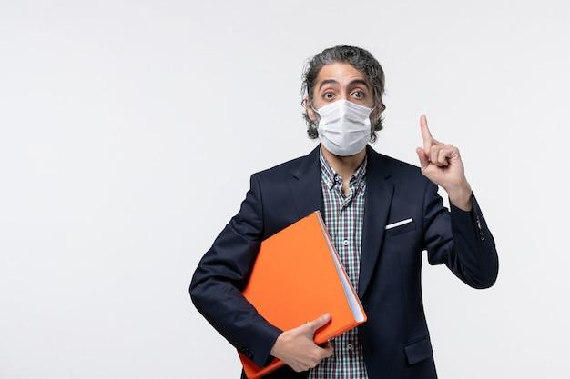 Biznesmen w garniturze i trzymający swoje dokumenty w masce chirurgicznej i wskazujący w górę na białej powierzchni