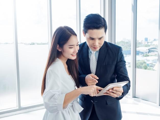 Biznesmen w garniturze i uśmiechnięta młoda kobieta, wskazując na cyfrowy tablet, jednocześnie oglądając na ekranie na szklanym oknie.