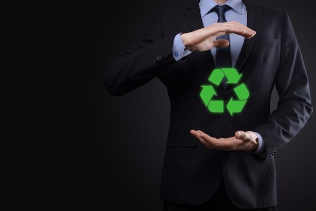 Biznesmen w garniturze na ciemnej powierzchni posiada ikonę recyklingu, zaloguj się w dłoniach