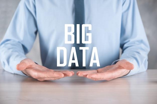 Biznesmen w garniturze na ciemnej powierzchni posiada napis big data