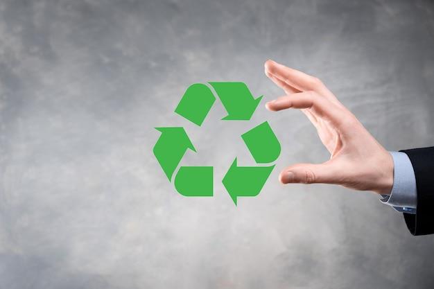 Biznesmen w garniturze na ciemnej ścianie posiada ikonę recyklingu, zaloguj się w jego ręce. koncepcja ekologii, środowiska i ochrony. neonowe czerwone niebieskie światło.