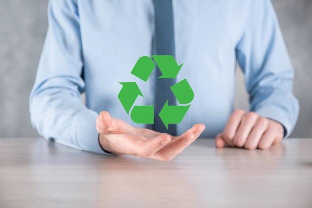 Biznesmen w garniturze na ciemnej ścianie posiada ikonę recyklingu, znak w jego rękach. koncepcja ekologii, środowiska i ochrony. neonowo czerwone światło niebieskie.