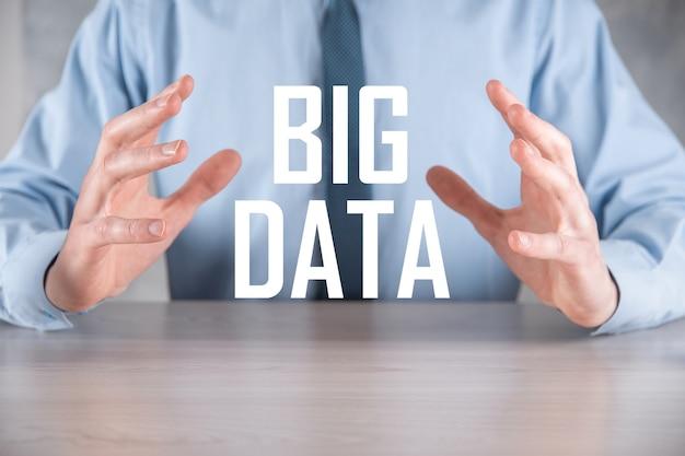 Biznesmen w garniturze na ciemnej ścianie posiada napis big data. storage network online server concept. reprezentacja sieci społecznościowej lub analizy biznesowej.