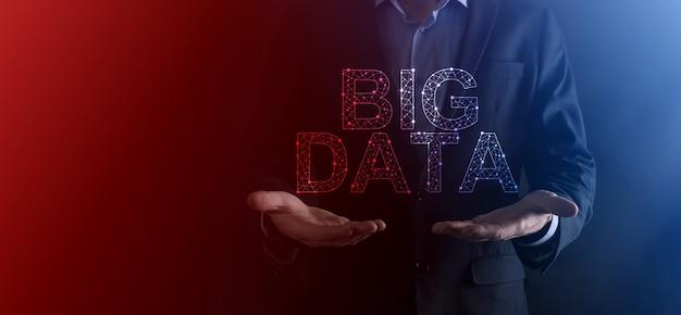 Biznesmen w garniturze na ciemnej ścianie trzyma napis big data. storage network online server concept. reprezentacja sieci społecznościowych lub analityki biznesowej. .