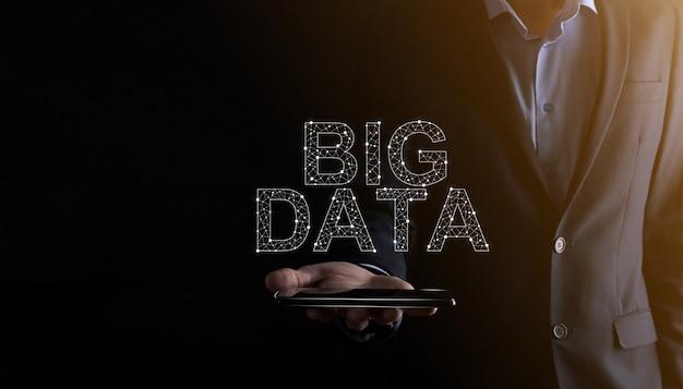 Biznesmen w garniturze na ciemnej ścianie trzyma napis big data. storage network online server concept. reprezentacja sieci społecznościowych lub analizy biznesowej.