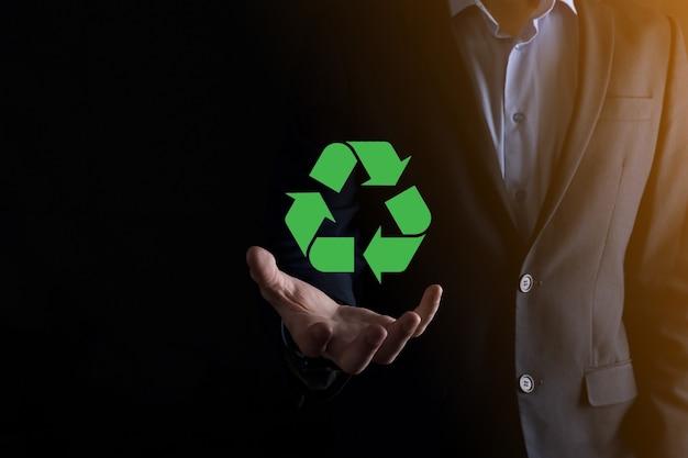 Biznesmen w garniturze na ciemnym tle posiada ikonę recyklingu, znak w jego rękach. koncepcja ekologii, środowiska i ochrony. neonowe czerwone niebieskie światło