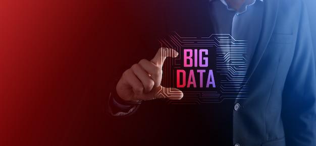 Biznesmen w garniturze na ciemnym tle posiada napis big data. koncepcja serwera sieci pamięci masowej online. reprezentacja sieci społecznościowych lub analityki biznesowej