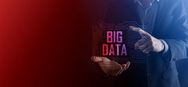 Biznesmen w garniturze na ciemnym tle posiada napis big data. storage network online server concept. reprezentacja sieci społecznościowej lub analizy biznesowej.