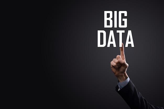 Biznesmen w garniturze na ciemnym tle posiada napis big data. storage network online server concept. reprezentacja sieci społecznościowych lub analizy biznesowej.