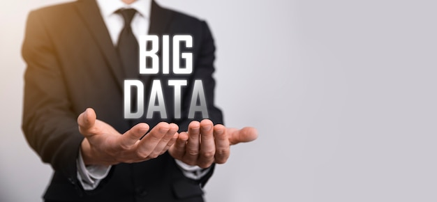 Biznesmen w garniturze na ciemnym tle trzyma napis big data. koncepcja serwera sieci pamięci masowej online. reprezentacja sieci społecznościowych lub analityki biznesowej