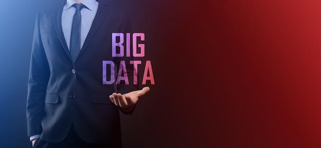 Biznesmen w garniturze na ciemnym tle trzyma napis big data. storage network online server concept. reprezentacja sieci społecznościowych lub analityki biznesowej. .