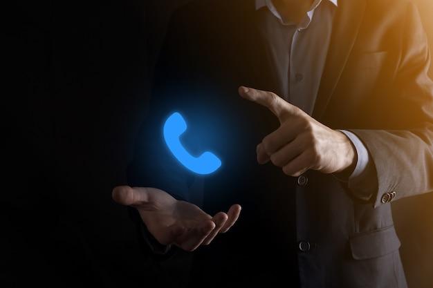 Biznesmen w garniturze na czarny kliknie ikonę telefonu.