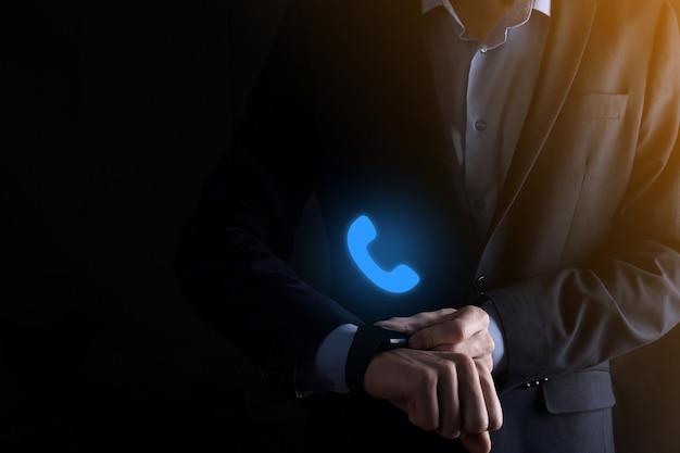 Biznesmen w garniturze na czarnym tle przytrzymaj ikonę telefonu. zadzwoń teraz do centrum wsparcia komunikacji biznesowej