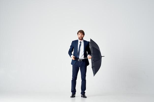 Biznesmen w garniturze parasol ochrona przed deszczem elegancki styl jasne tło