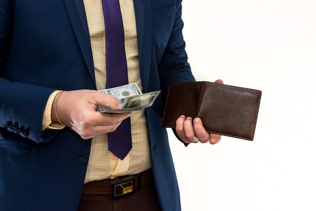 Biznesmen w garniturze pobiera nam pieniądze z portfela na białym tle
