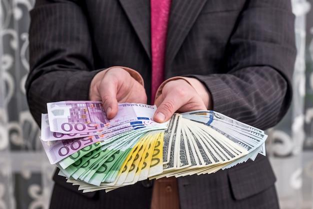 Biznesmen w garniturze pokazując i oferując banknoty euro i dolara