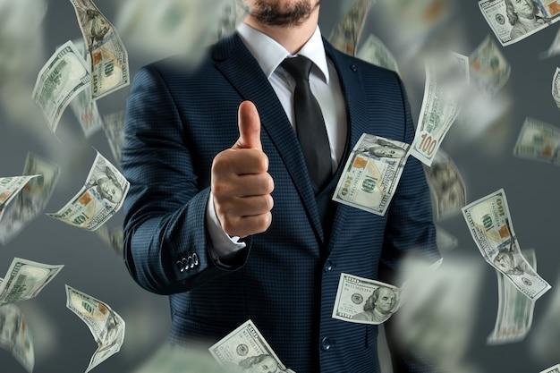 Biznesmen w garniturze pokazuje kciuki do góry na tle spadających dolarów. pojęcie inwestycji, dywidend, odsetek, lokat bankowych.