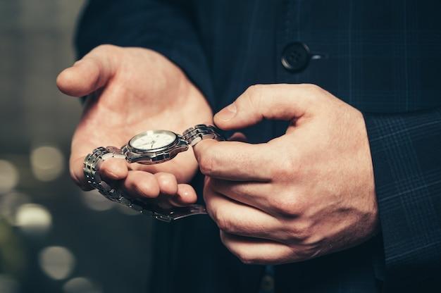 Biznesmen w garniturze pokazuje swój zegarek na rękę.