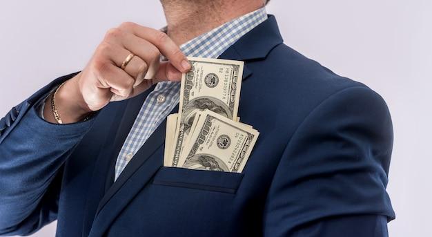 Biznesmen w garniturze posiada dolary, dużo pieniędzy, na białym tle. koncepcja finansów