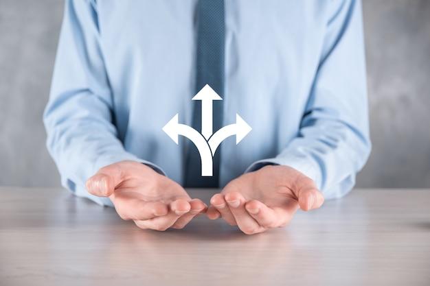 Biznesmen w garniturze posiada znak przedstawiający trzy kierunki. w razie wątpliwości, mając do wyboru trzy różne opcje zaznaczone strzałkami wskazującymi w przeciwnym kierunku. trzy sposoby wyboru