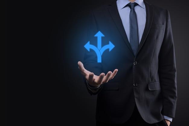 Biznesmen w garniturze posiada znak przedstawiający trzy kierunki