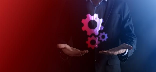 Biznesmen w garniturze posiadający metalowe koła zębate i mechanizm koła zębatego reprezentujący koncepcję pracy zespołowej interakcji, ręka trzymaj grupę kół zębatych wirtualnych kół zębatych.