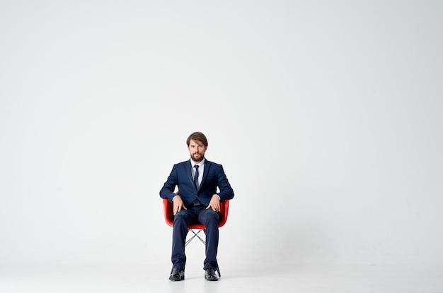 Biznesmen w garniturze siedzi na czerwonych krzesłach kierownik biura pracy