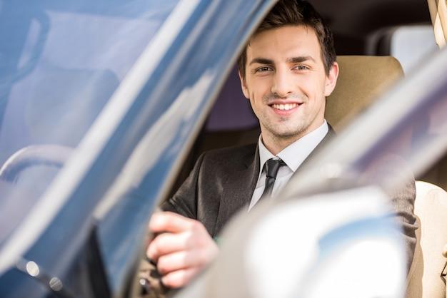Biznesmen w garniturze siedzi w swoim luksusowym samochodzie.