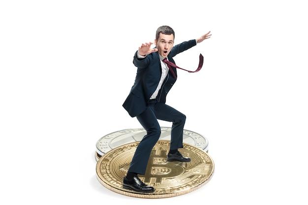 Biznesmen w garniturze stojący na ikonę wielkiego biznesu. męska figura i litecoin na białym tle. kryptowaluta, bitcoin, ethereum, e-commerce, koncepcja finansów. kolaż