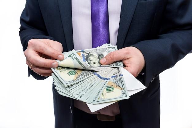 Biznesmen w garniturze trzyma kopertę z banknotami dolarowymi