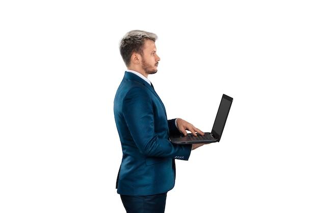 Biznesmen w garniturze trzyma laptopa na białym tle