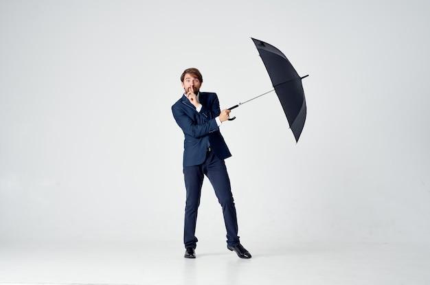Biznesmen w garniturze trzyma parasol w eleganckim stylu ochrony przed deszczem