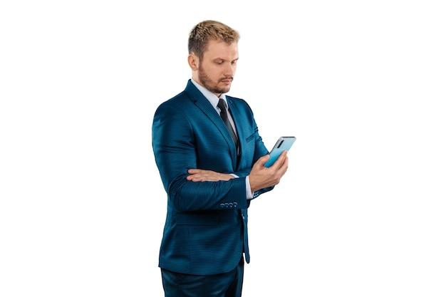 Biznesmen w garniturze trzyma smartfon w jego rękach na białym tle