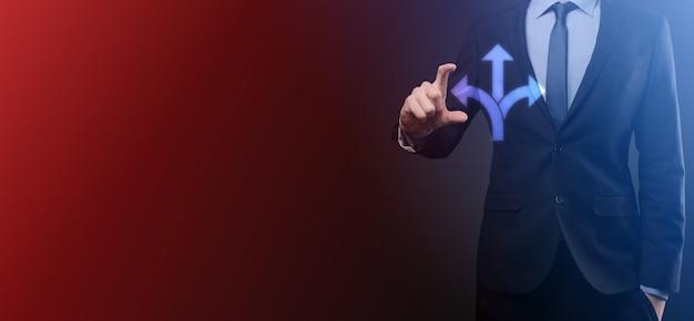 Biznesmen w garniturze trzyma znak wskazujący trzy kierunki, w których wątpię, musi wybierać między trzema różnymi możliwościami wskazanymi przez strzałki wskazujące w przeciwnym kierunku koncepcja trzy sposoby wyboru